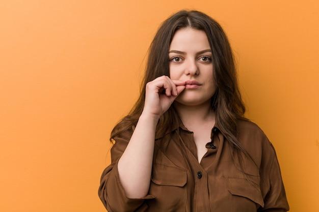 Giovane donna russa curvy con le dita sulle labbra mantenendo un segreto.