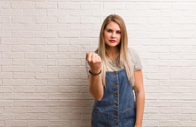 Giovane donna russa dei pantaloni a vita bassa che mostra pugno alla fronte, espressione arrabbiata