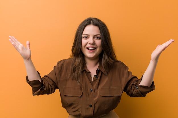 Giovane donna russa formosa che riceve una piacevole sorpresa, eccitata e alzando le mani.