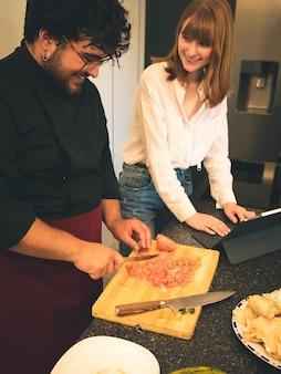 Giovane donna russa rossa dei capelli con una compressa che guarda i suoi pomodori di taglio dell'insegnante di cucina