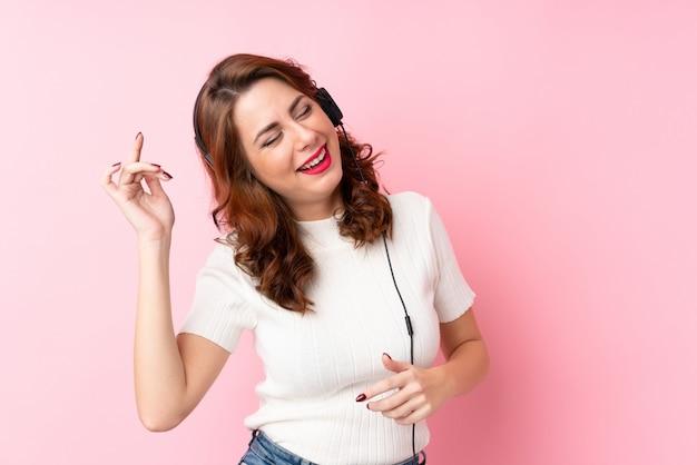 Giovane donna russa sopra fondo rosa isolato usando il cellulare con le cuffie e ballare