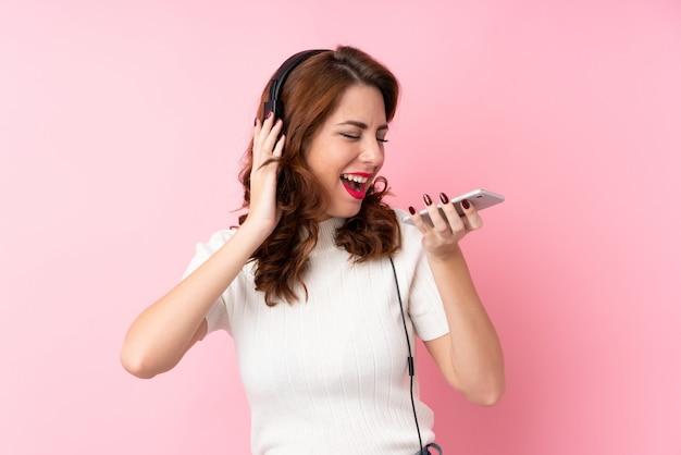 Giovane donna russa sopra il rosa isolato usando il cellulare con le cuffie e il canto