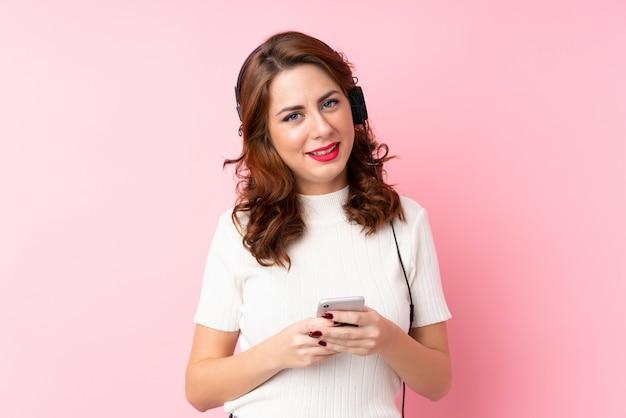 Giovane donna russa su sfondo rosa isolato utilizzando il cellulare con le cuffie