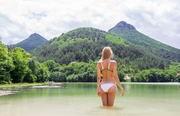 Giovane donna sbalorditiva in bikini bianco che sta nel lago