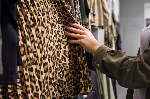 Giovane donna scegliendo diversi abiti