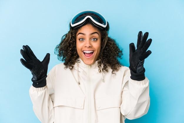 Giovane donna sciatore afroamericano isolato ricevendo una piacevole sorpresa, eccitato e alzando le mani.