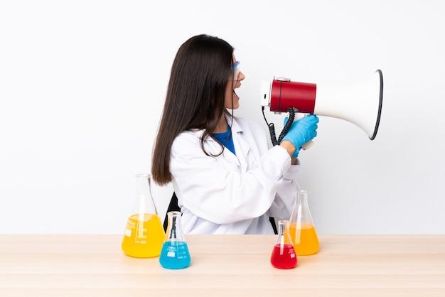 Giovane donna scientifica in una tabella che grida tramite un megafono