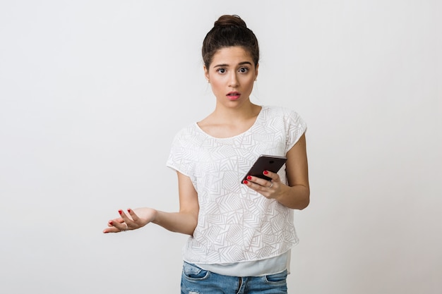 Giovane donna scioccata che tiene smart phone, bocca aperta, espressione del viso sorpreso, isolato, con un problema