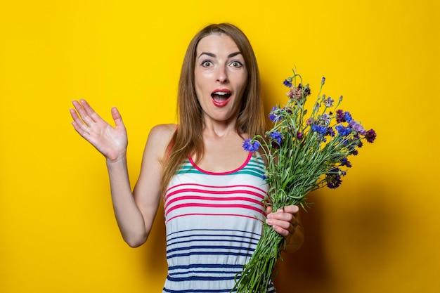 Giovane donna scioccata sorpresa in vestito a strisce che tiene i fiori di campo