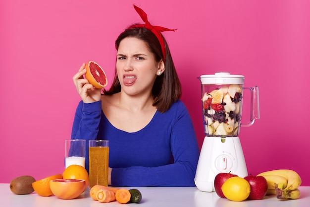 Giovane donna scontenta con la fascia rossa brillante in testa, indossa una felpa blu scuro, mostra la lingua con disgusto