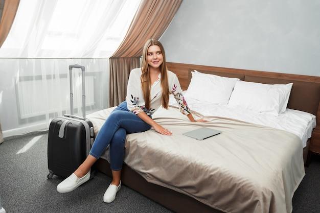 Giovane donna sdraiata nel letto di una camera d'albergo