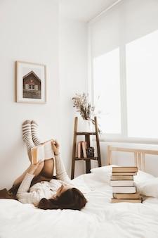 Giovane donna sdraiata sul letto con il libro
