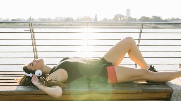 Giovane donna sdraiata sulla panchina ascoltando musica in cuffia