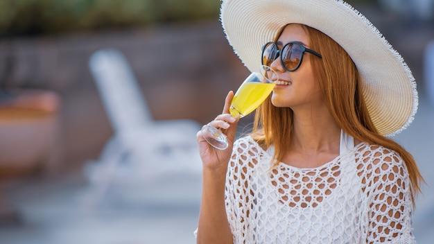 Giovane donna seduta accanto a piscina con un bicchiere in vacanza felice.