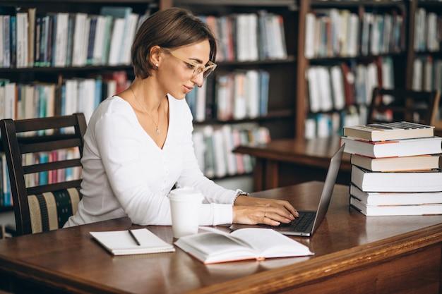Giovane donna seduta in biblioteca utilizzando libri e computer