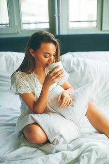 Giovane donna seduta su un letto e bere caffè dopo svegliarsi