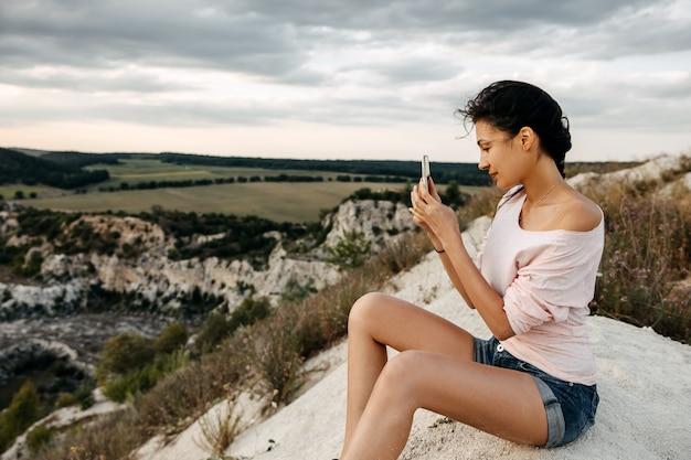Giovane donna seduta su una cima della montagna a scattare foto del paesaggio con lo smartphone.