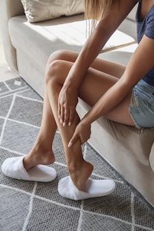 Giovane donna seduta sul divano che soffre di dolori alle gambe a casa