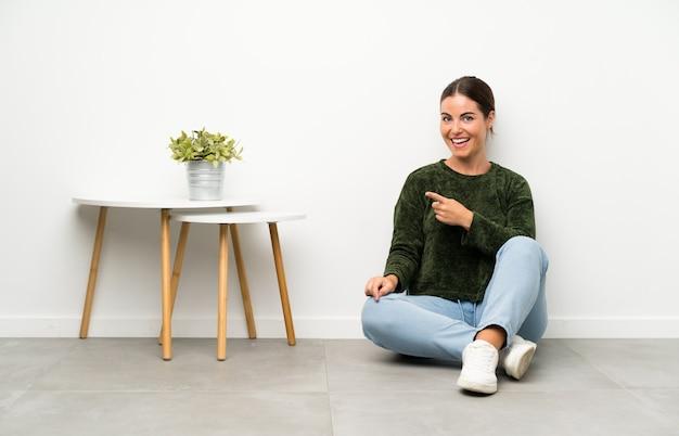 Giovane donna seduta sul pavimento che punta il dito verso il lato