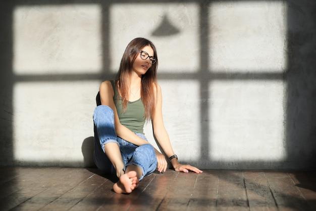 Giovane donna seduta sul pavimento di una stanza vuota