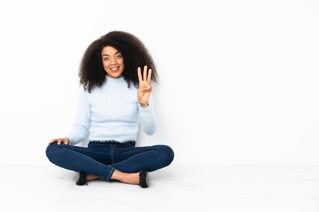 Giovane donna seduta sul pavimento felice e contando tre con le dita
