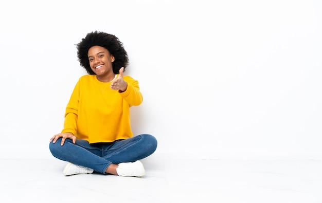 Giovane donna seduta sul pavimento si stringono la mano per chiudere un buon affare