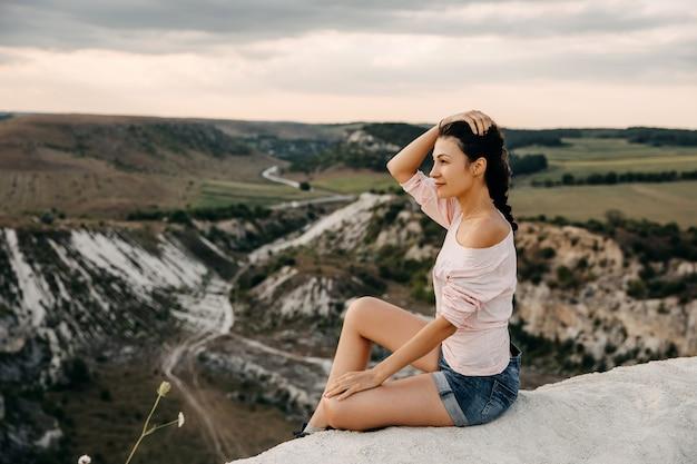 Giovane donna seduta sulla cima di una collina a guardare i paesaggi.