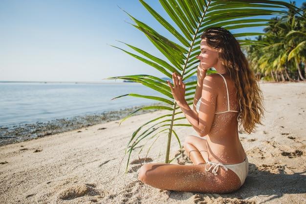 Giovane donna seduta sulla spiaggia di sabbia sotto la foglia di palma