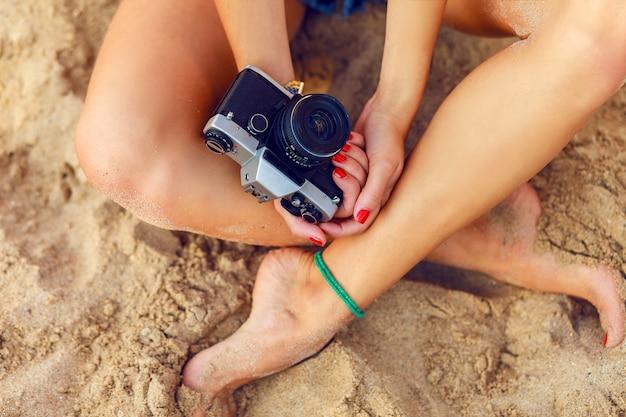 Giovane donna seduta sulla spiaggia tropicale calda una fotocamera retrò della holding