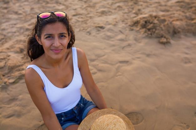 Giovane donna seduta sulla spiaggia