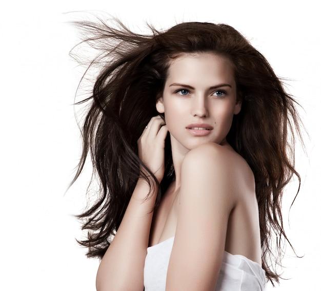 Giovane donna sensuale con bei capelli marroni lunghi di volo, posante i