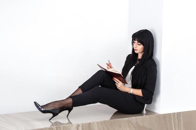 Giovane donna seria attraente che si siede su un pavimento in un ufficio, leggente in un taccuino.