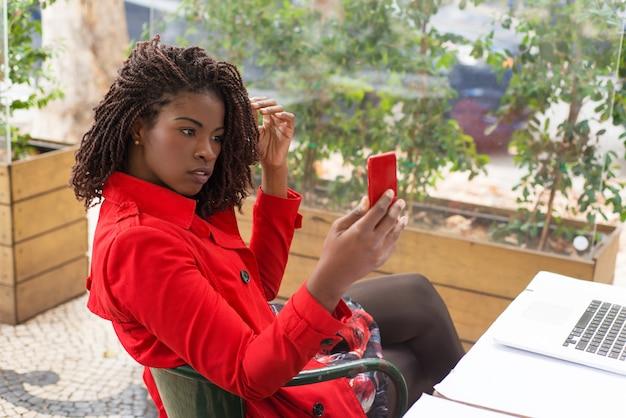 Giovane donna seria che per mezzo del telefono cellulare