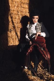 Giovane donna seria che si siede nel granaio con seddle