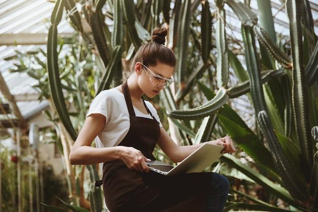 Giovane donna seria che si siede nella serra facendo uso del computer portatile