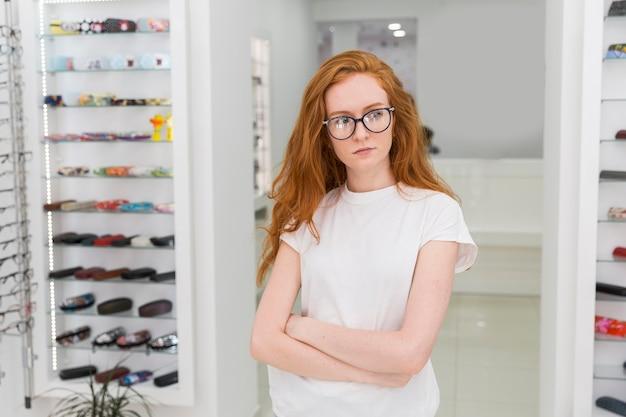 Giovane donna seria che sta nel negozio di ottica con il braccio attraversato