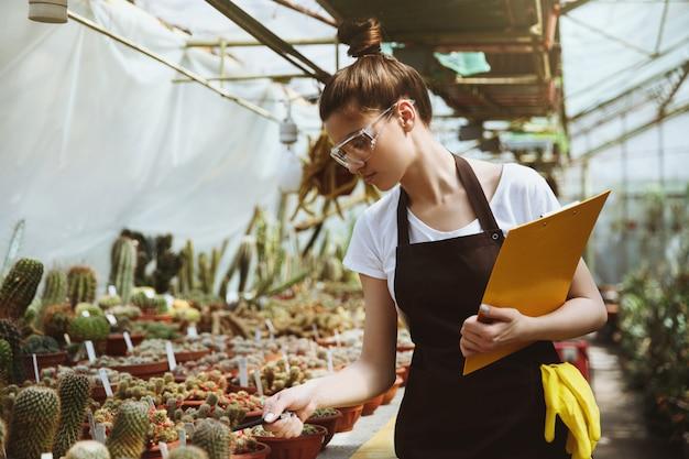 Giovane donna seria che sta nella lavagna per appunti della tenuta della serra
