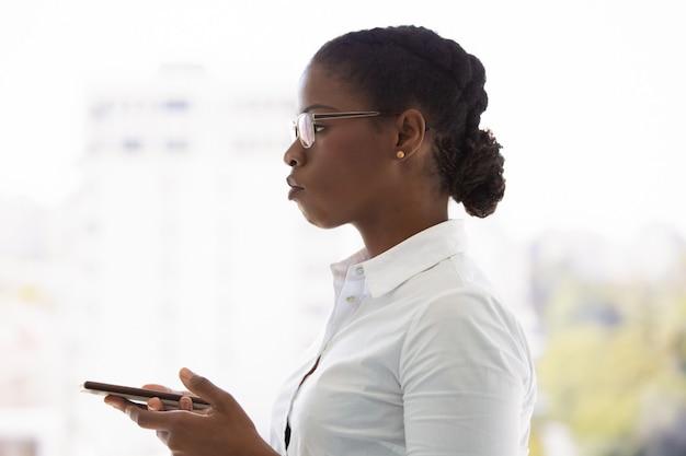Giovane donna seria di affari che per mezzo del telefono cellulare