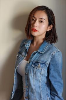 Giovane donna sexy asiatica adulta di vista frontale, labbro rosso e capelli corti in jeans blu con la condizione del fronte di bellezza.