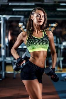 Giovane donna sexy atletica di forma fisica sul treno di dieta ed esercitarsi in palestra