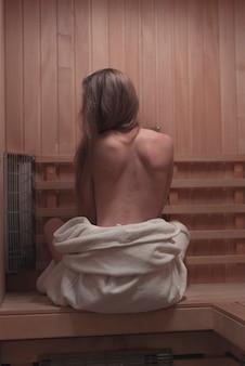 Giovane donna sexy backless che si siede sul banco nella sauna