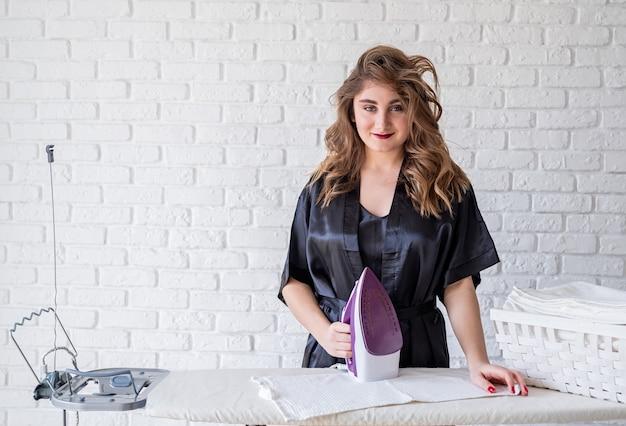 Giovane donna sexy che riveste di ferro a casa con lo spazio della copia