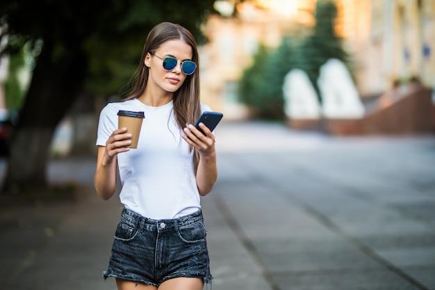 Giovane donna sexy con caffè da andare e telefono che cammina sulla strada estate