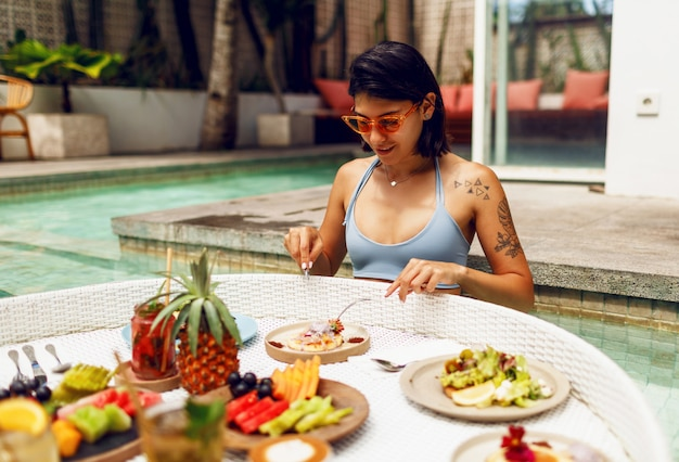 Giovane donna sexy con il tatuaggio in costume da bagno facendo colazione in una piscina privata. ragazza rilassante in piscina bevendo caffè e mangiando frutta. piatto di frutta, frullato a bordo piscina.