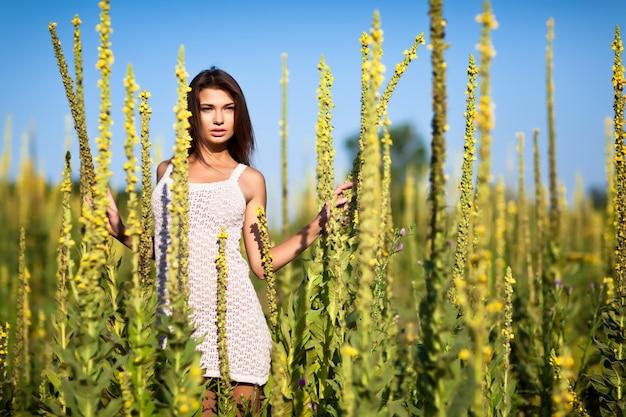 Giovane donna sexy del brunette in vestito bianco che sta e che gode del sole in alta erba il giorno di estate