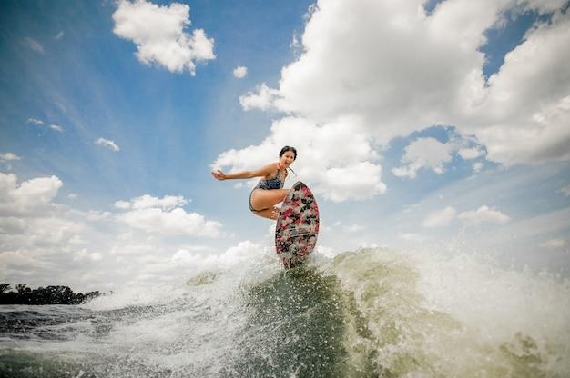 Giovane donna sexy divertendosi wakesurfing anf che salta sul bordo