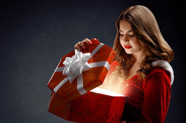 Giovane donna sexy in abito rosso di babbo natale con doni. su un da
