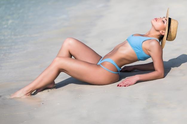 Giovane donna sexy in bikini con cappello di paglia in spiaggia tropicale
