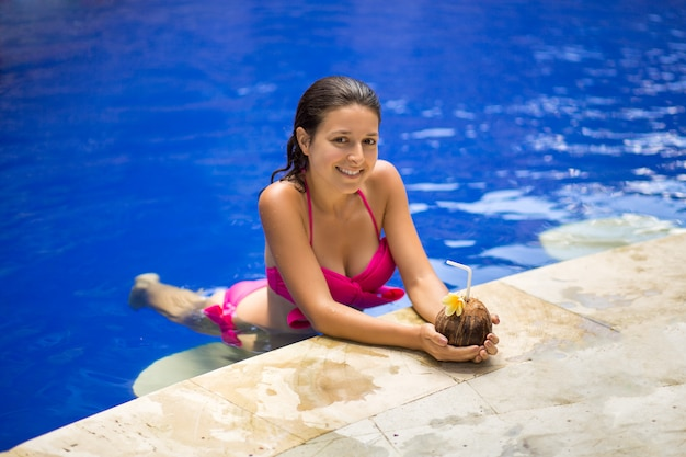 Giovane donna sexy in costume da bagno rosa con la bevanda di cocco in piscina in vacanza