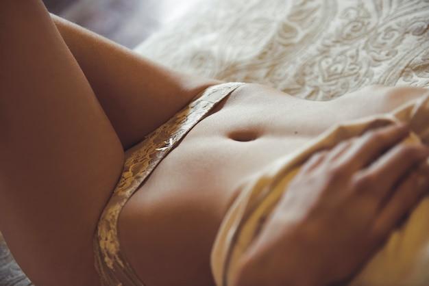 Giovane donna sexy in lingerie in posa sul letto